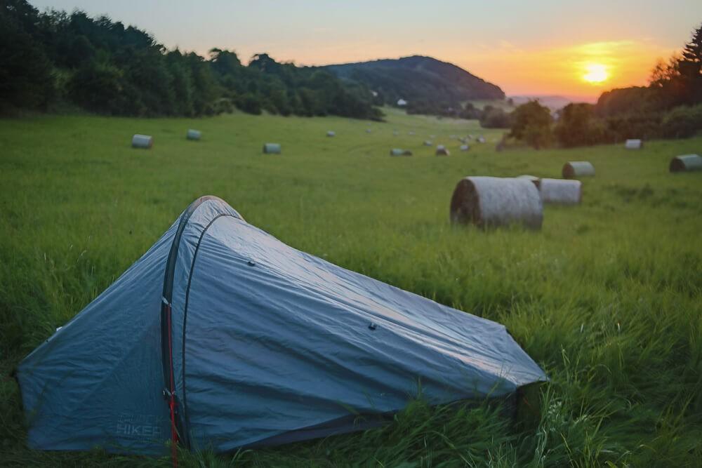 Zelt mit Heuballen und Sonnenuntergang im Hintergrund