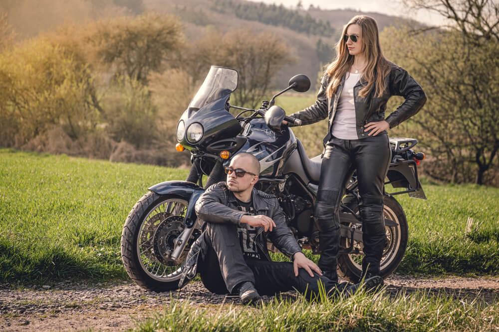 Nicki und Moe posen mit SOnnenbrille und Lederjacke vor dem Triumph Tiger t709