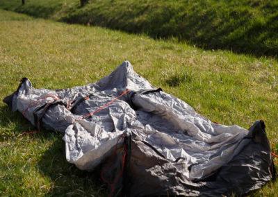Die Zeltplane auf dem Boden ausgebreitet.
