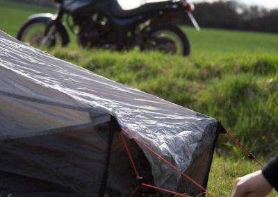 Der Zeltaufbau im Vordergrund, das Motorrad im Hintergrund