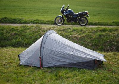 Das Zelt im Vordergrund auf einer Wiese, das Motorrad im Hintergrund