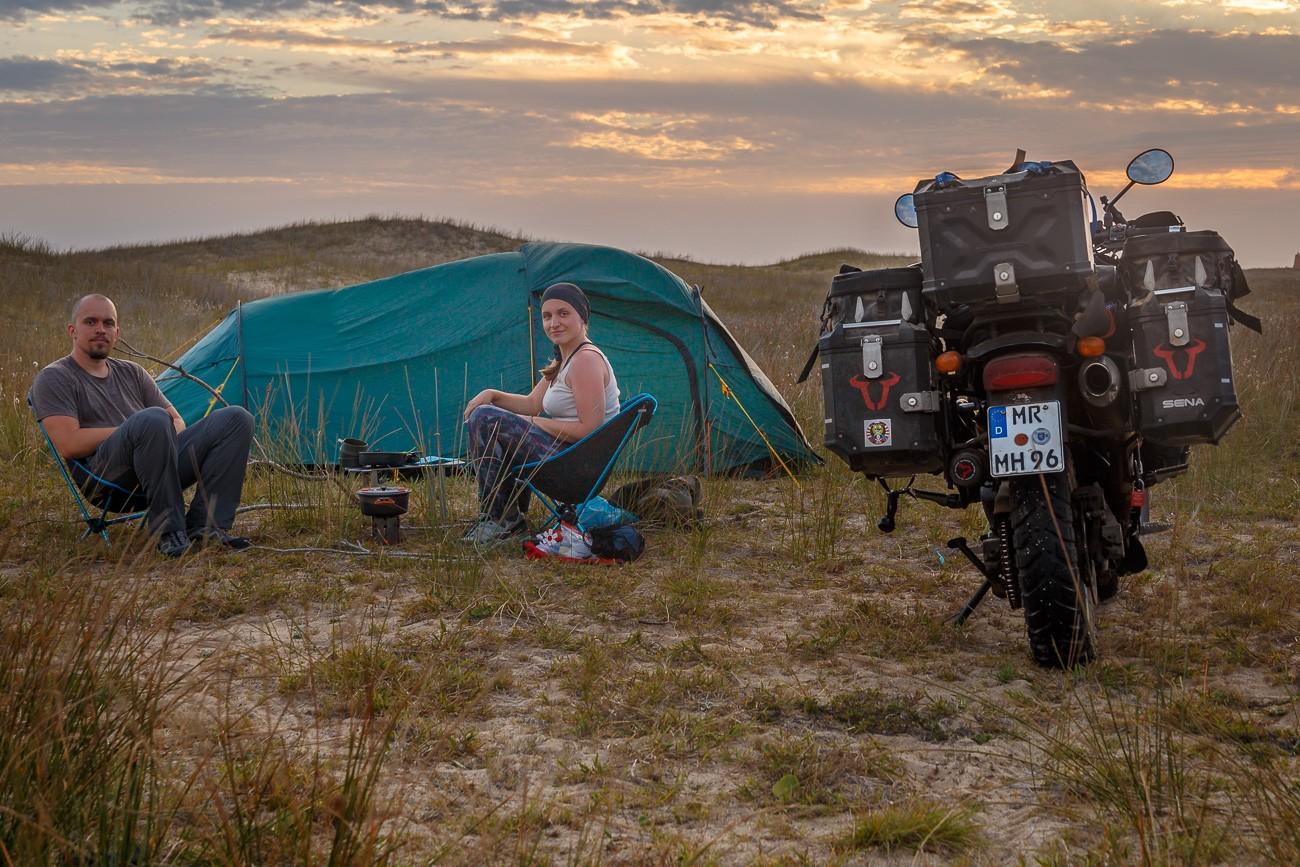 Nicki und Moe sitzen an den Dünen vor ihren Zelt, das Motorrad steht direkt daneben
