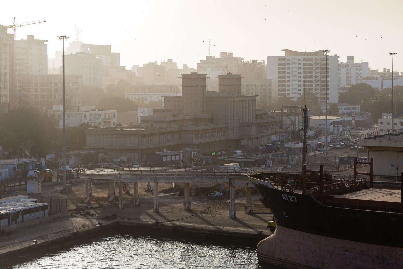 Blick aus dem Hafen auf die Skyline von Dakar, die im Nebel verschwindet