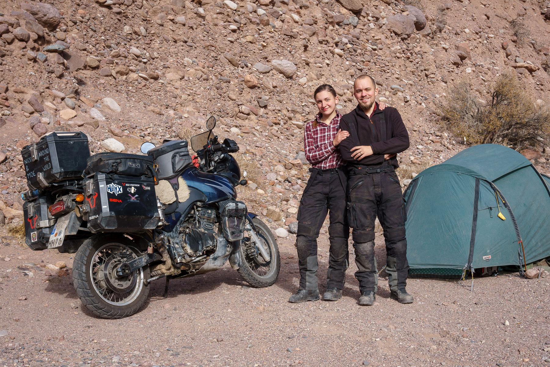 Nicki and Moe standing happily in front of the tent and the motorcycle