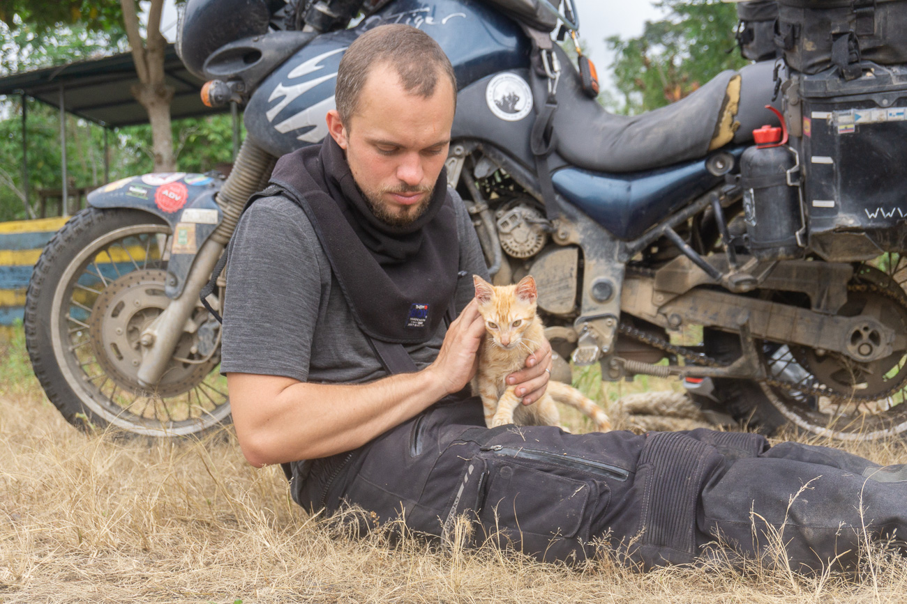 Cat on the lap of Moe in front of the motorcycle